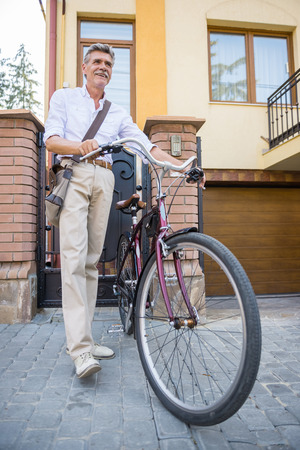 vertica: Senior man is walking with bike in the street.
