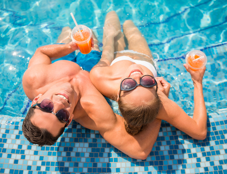 Top view of young couple relaxing in resort swimming pool and drinking cocktails.