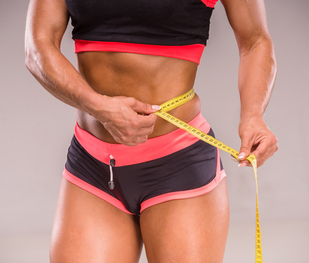 measuring waist: Muscular woman is measuring waist of perfect body.
