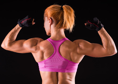 showing muscles: Rear view of athletic woman is showing muscles of the back and hands on a dark background. Stock Photo