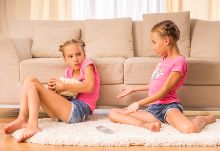 twin sister: One of sisters hides a bucket of popcorn while watching tv with her twin sister. Stock Photo