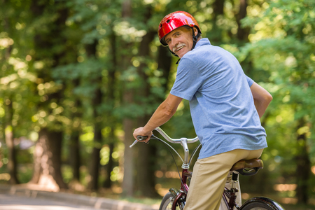 1 mature man: Rear view of senior man in helmet is riding bicycle in park and looking over shoulder.