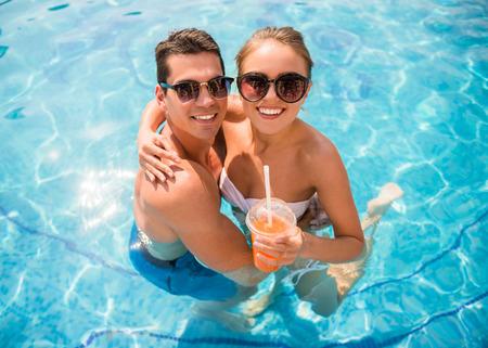 parejas: Vista superior de la joven pareja se relaja en piscina del centro tur�stico y beber c�cteles. Foto de archivo