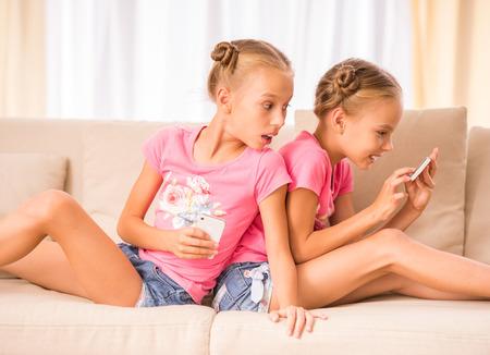 gemelas: Gemelos hermanas jóvenes están utilizando teléfono inteligente sentado en el sofá. Foto de archivo