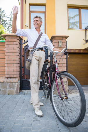 vertica: Senior man with bike in the street saying hello to neighbours.