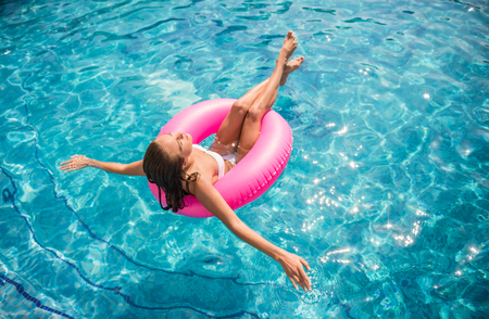 fun: Young beautiful woman is relaxing in swimming pool with rubber ring. Stock Photo