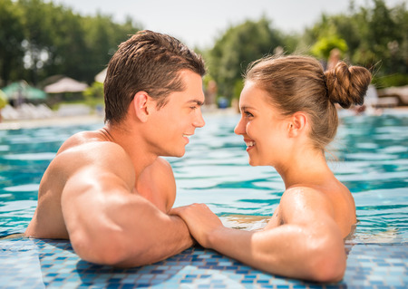Young couple in pool. They are looking at each other and smiling.