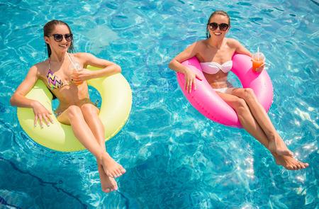 schwimmring: Fröhliche Freundinnen haben Spaß im Pool und trinken Cocktails.
