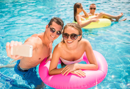 Happy young couple are making selfie while having fun in pool.