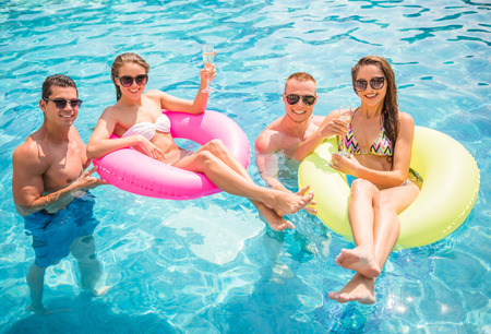 Beautiful young people having fun in swimming pool, smiling and drinking champagne. Stock Photo