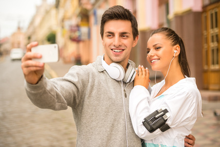 Young people in sports wear are taking a selfie photo standing on the street. Stock Photo
