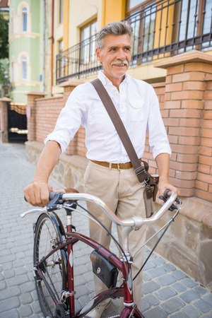 vertica: Senior man with his bike in public streets in town. Concept of active life elderly people.