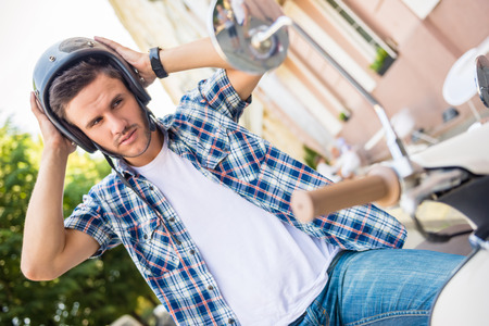 casco de moto: Hombre joven hermoso que lleva el casco mientras se está sentado en la vespa. Foto de archivo