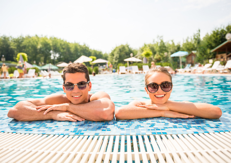 luxury travel: Young couple relaxing in resort swimming pool. Stock Photo