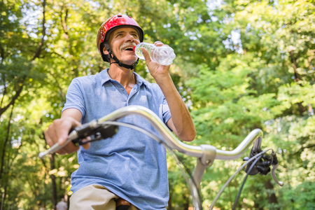 Senior man in helmet is drinking water while riding bicycle in park. Stock Photo
