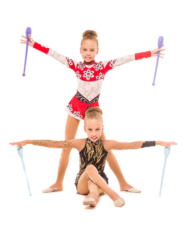 mace: Twins girls exercising with gymnastic mace isolated on white background.