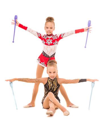 gimnasia ritmica: Twins ni�as que ejercitan con la maza de gimnasia aislada en el fondo blanco. Foto de archivo