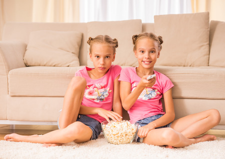 Twins sisters are watching tv and eating popcorn sitting on the floor.