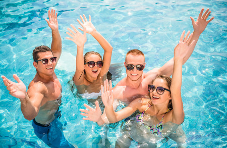 Beautiful young people having fun in swimming pool, smiling. Stock Photo