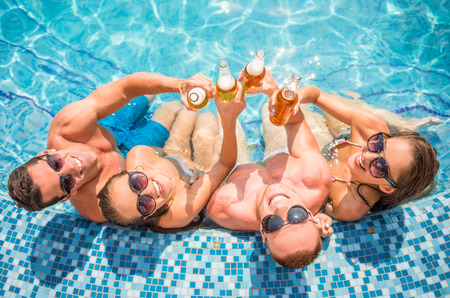 Top view of beautiful young people having fun in swimming pool, smiling and drinking beer.