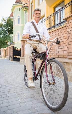 vertica: Senior man is riding bike in public street in town. Concept of active life elderly people.