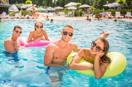 bikini couple: Beautiful young people having fun in swimming pool, smiling. Stock Photo