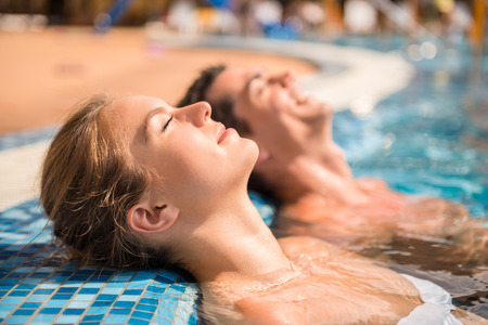 relajado: Joven pareja se relaja en la piscina.