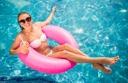 若くてきれいな女性はゴム輪とカクテル付きのスイミング プールでリラックスです。