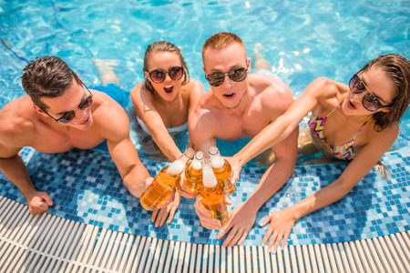 bikini couple: Beautiful young people having fun in swimming pool, smiling and drinking beer.