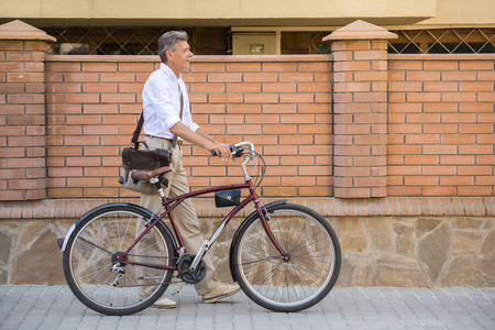 personas en la calle: Side view of senior man is walking with bike in the street.