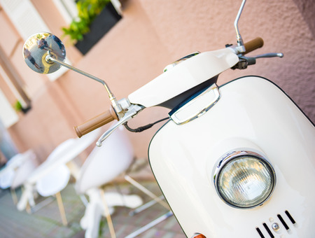 mope: Close-up picture of vintage white scooter, outdoors. Stock Photo