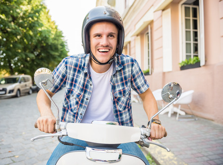 Cheerful young man in helmet is riding on scooter in town. Stock Photo