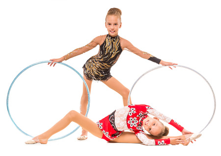 hoops: Twins girls doing gymnastics exercises with hoops on a white background.