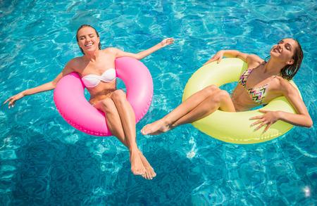 Fröhliche Freundinnen haben Spaß im Schwimmbad.