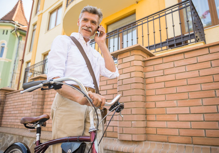 vertica: Senior man is talking by phone standing with bike in the street. Concept of active life elderly people.