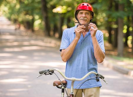 Smiling senior man is wearing helmet while sitting on bicycle. Stock Photo