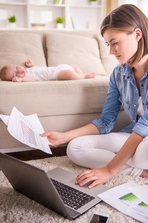 Junge Frau arbeitet zu Hause, während ihr kleines Baby schläft.