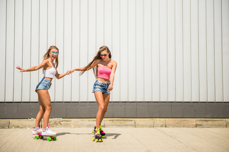 rollers: Two female friends are riding in rollers and skateboard.