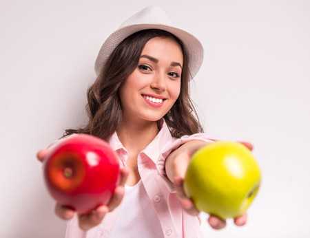 sexual selection: Young smiling woman is holding red and green apple.