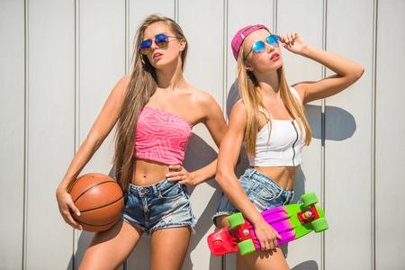 urban colors: hermosas mujeres jóvenes con bola y el patín de pie contra la pared, al aire libre. Foto de archivo