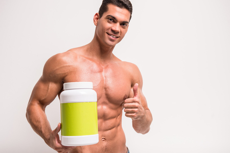 mamadera: Smiling muscular man with jar of protein. Sports nutrition.