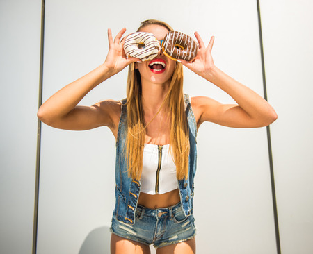 Playful young woman holding donuts against her eyes and smiling while standing against the wall. Stock Photo