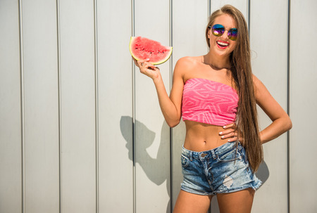 happy life: Happy young woman is holding a slice of watermelon standing against the wall.