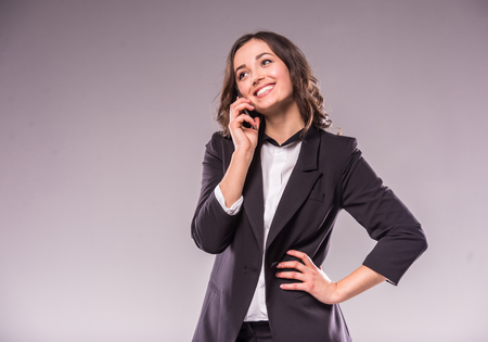 telephone saleswoman: Happy young woman is talking by phone on grey background.