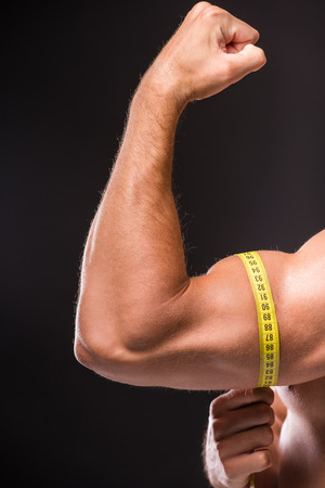 tricep: Muscular man is measuring arm, bicep and tricep with tape measure, close-up of arm on dark background. Stock Photo