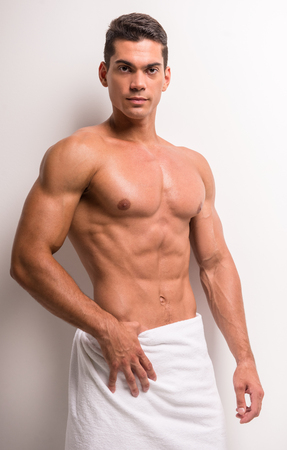 naked male body: Young shirtless man covered with towel standing against white background. Stock Photo
