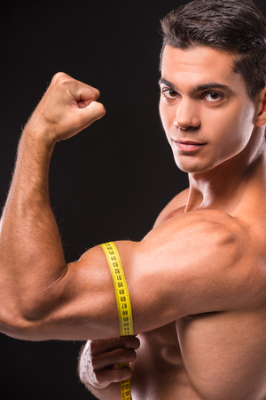 tricep: Muscular shirtless young man is measuring arm, bicep and tricep with tape measure. Dark background.