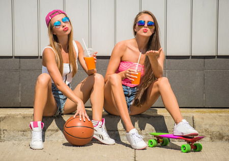 tomando jugo: Two playful girls with basketball and skateboard and drinking juice. Foto de archivo