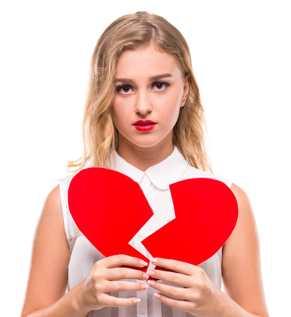 Young woman is holding a broken heart isolated on white background. Stock Photo