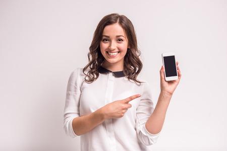 sonriente: Mujer sonriente que se�ala en el tel�fono inteligente de pie sobre fondo blanco.